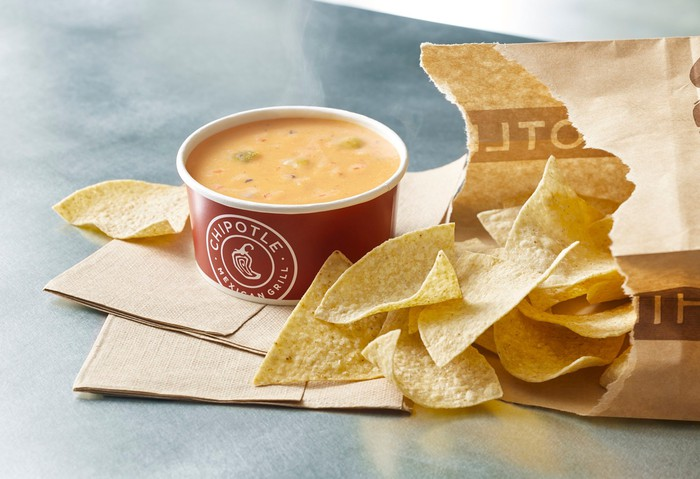 A cup of Chipotle queso next to a bag of tortilla chips