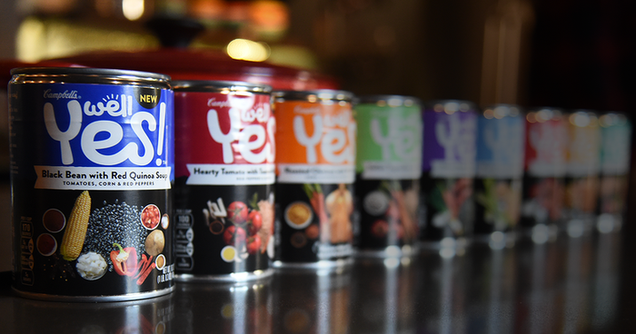 """Cans of Campbell's """"Well Yes!"""" soups lined up on table."""
