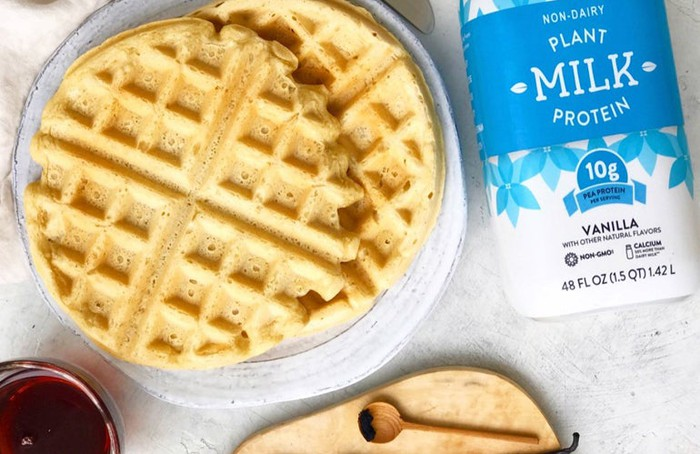 Waffles on a plate with bottle of Bolthouse Farms plant protein milk drink on table.