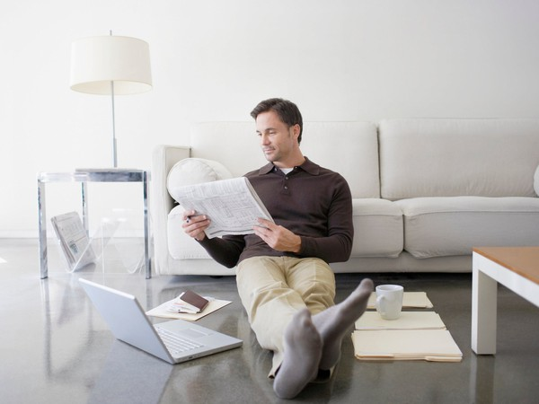 man reading stock quotes in newspaper
