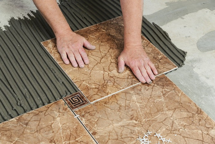 A worker laying brown tile on a floor.