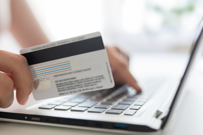 A person holds a credit card next to a laptop keyboard.