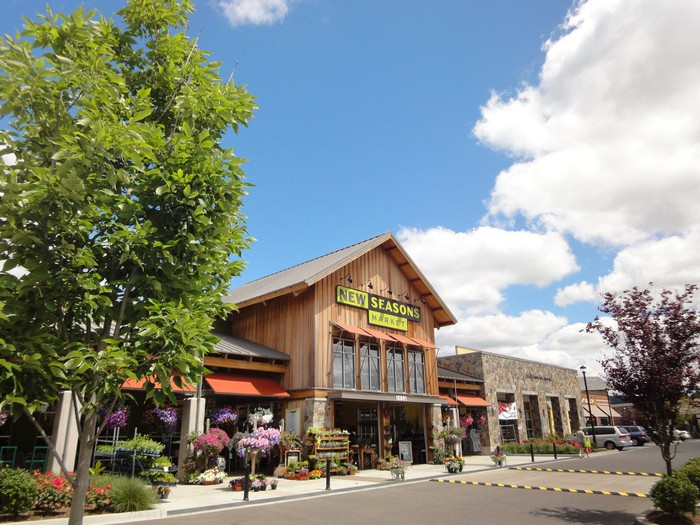 A grocery store named New Seasons Market with flowers and trees in front and under blue skies