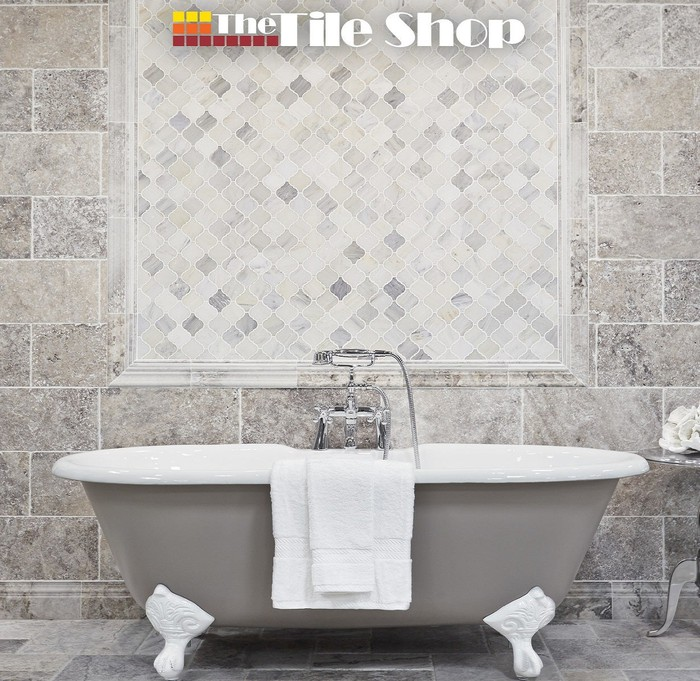 Four-leg tub in front of a tiled wall.