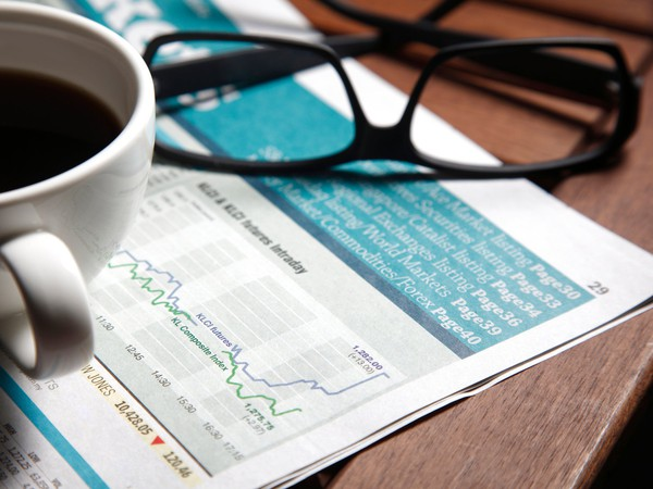 financial newspaper with coffee mug and spectacles sitting on top of it investing markets media finance