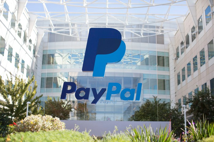A blue PayPal sign on glass surrounded by shrubbery in front of its headquarters.