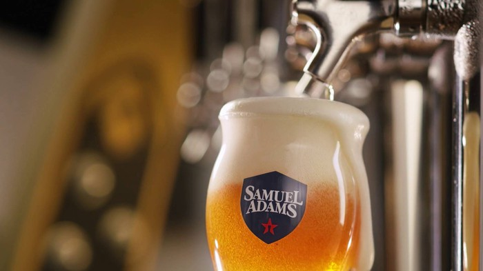 A glass of Samuel Adams beer on tap.