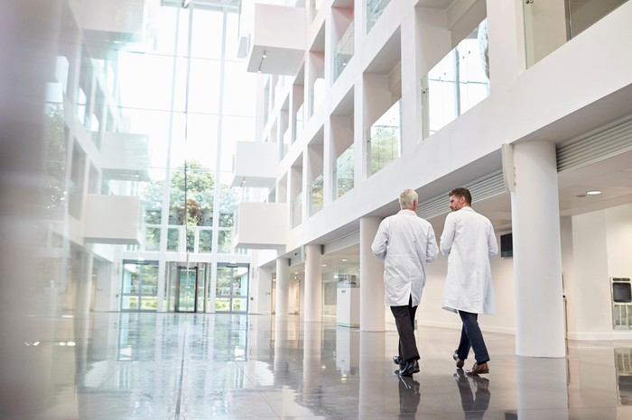 Two people in lab coats talking as they walk through the lobby of a building.