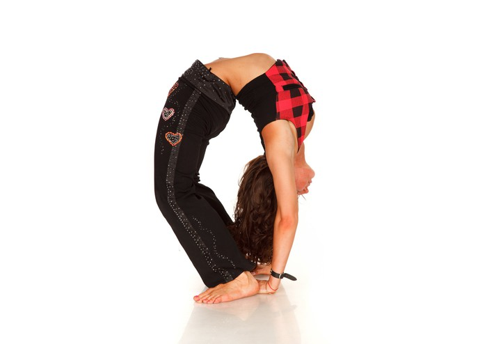 Young woman bending over backwards, to the point where her hands are tucked under her heels.