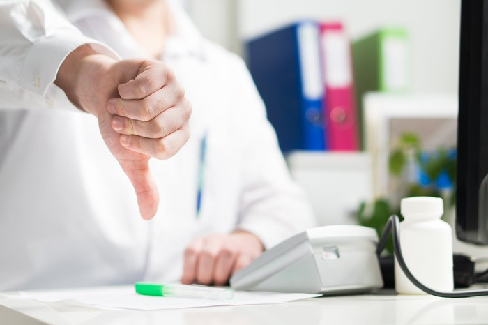 Doctor sitting in office with his thumb pointing down.
