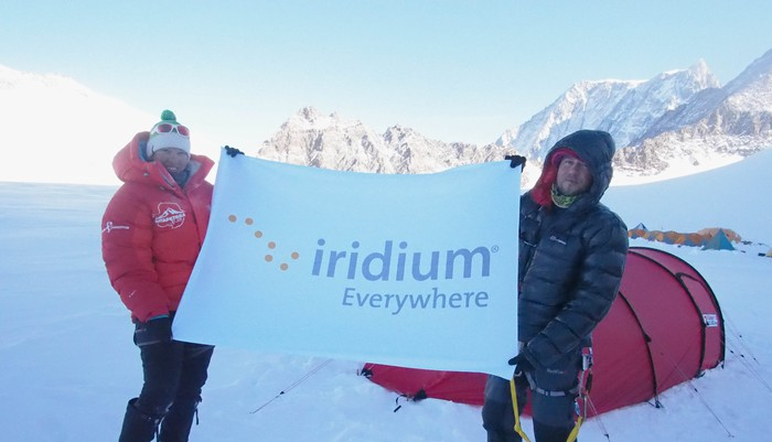 Two people in a winter setting holding a sign saying Iridium Everywhere.