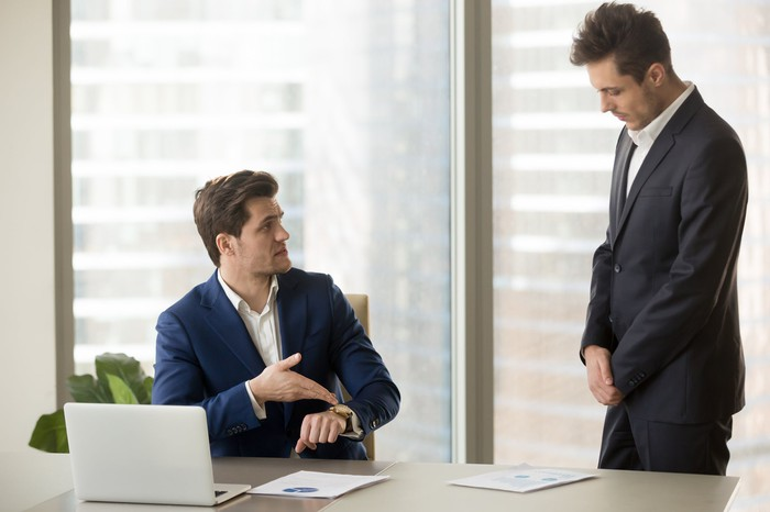 Professional man at desk points at his watch while another professional man stands nearby with his head down