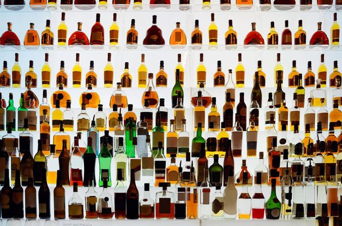 A large shelf of liquor bottles backlit with white lights.