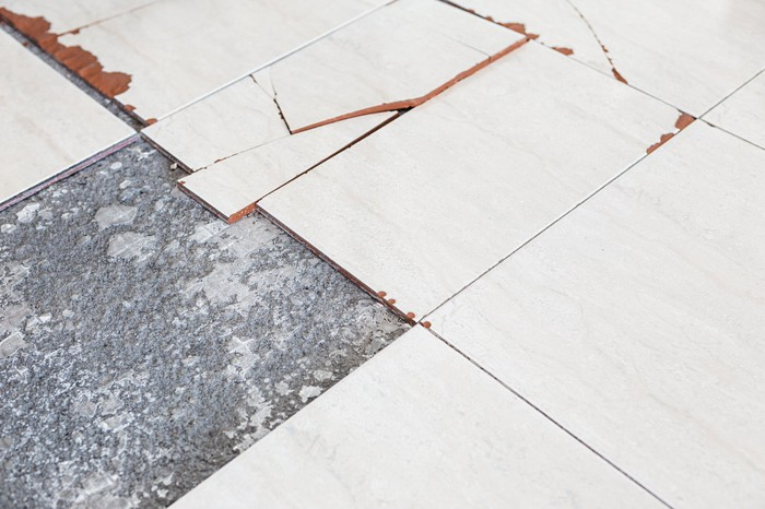 Close-up shot of a few ceramic floor tiles, cracked and damaged.