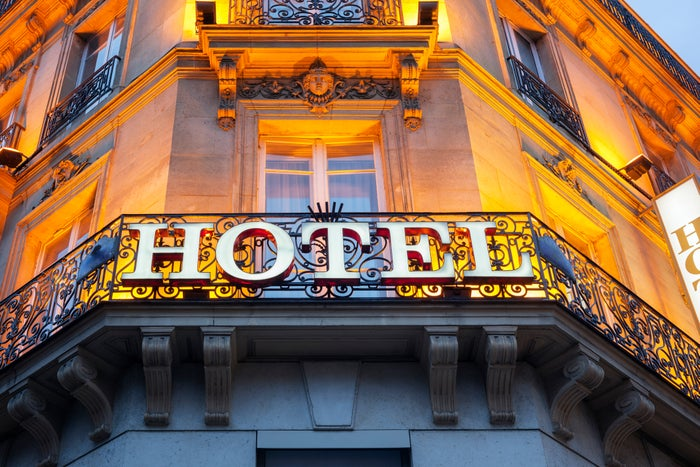 The facade of a hotel bathed in yellow light.