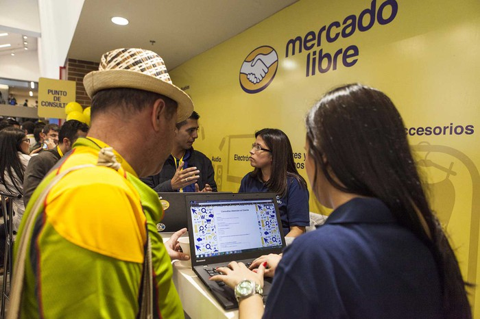 Two people looking at computer screen in front of a wall with the MercadoLibre logo on it.
