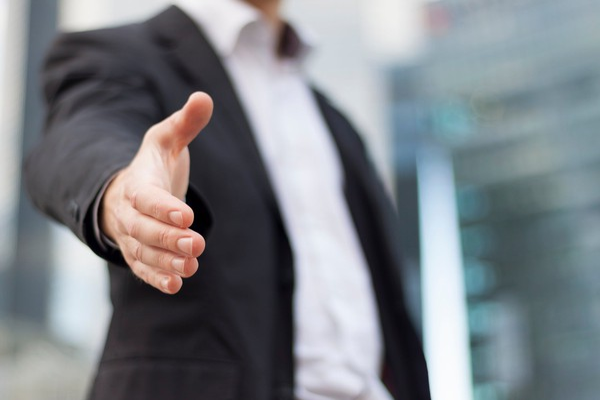 man in suit extending a handshake_GettyImages-186347725