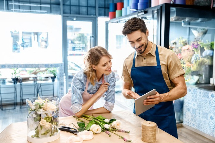 Two young florists using tablet device in their shop while putting together a flower arrangement.
