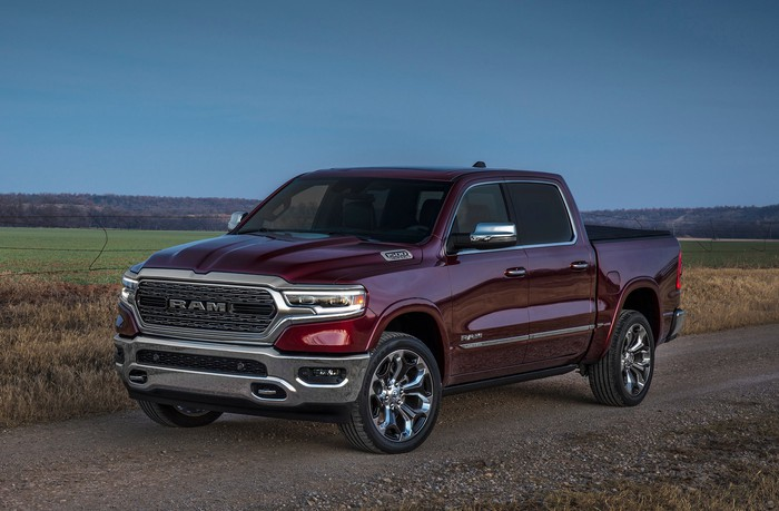 A dark red 2019 Ram 1500, a full-size pickup truck, parked next to a farm field.