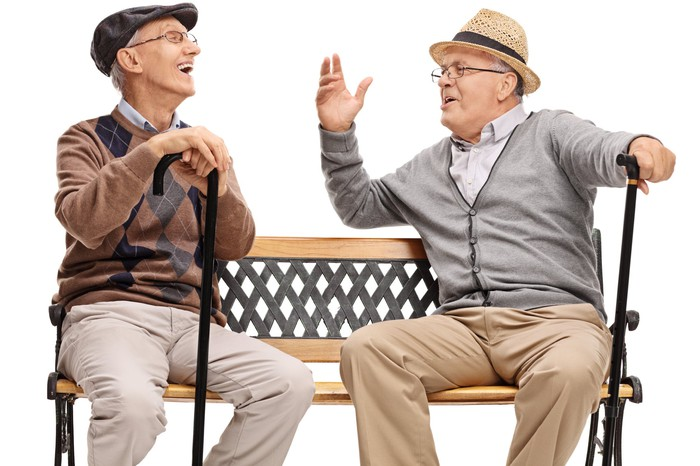 Two old men with canes, sitting on a bench talking and laughing