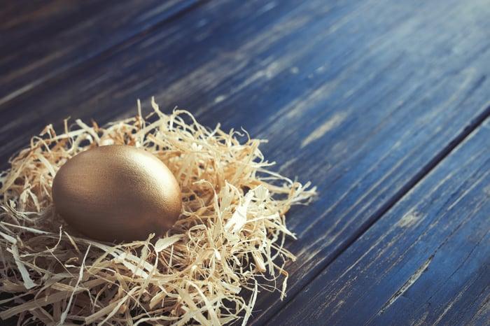 A golden egg in a nest that's on top of a dark wooden plank