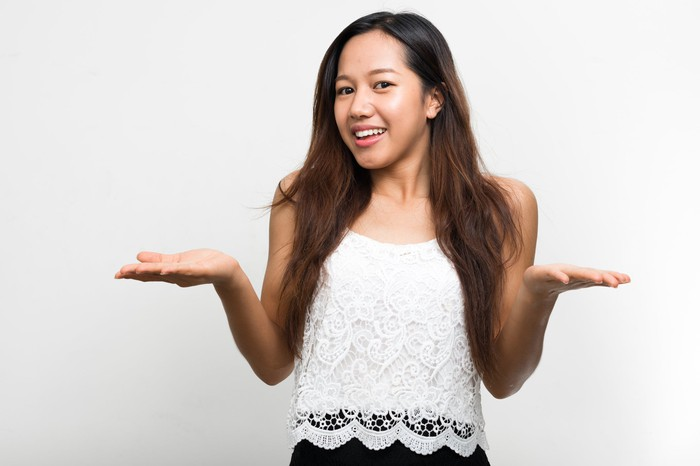 A millennial woman with long hair smiling and shrugging her arms and shoulders.