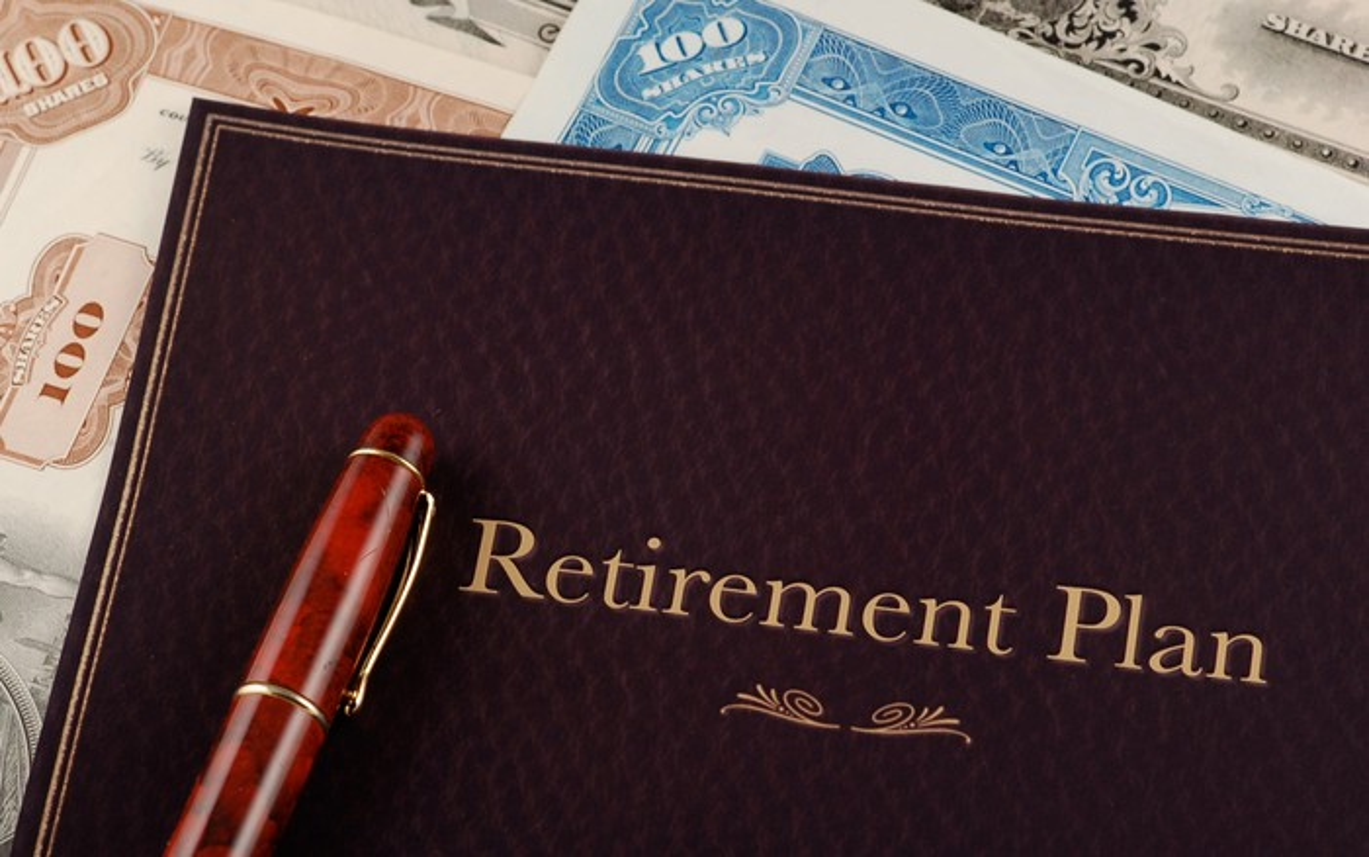Retirement plan portfolio on top of stock certificates.