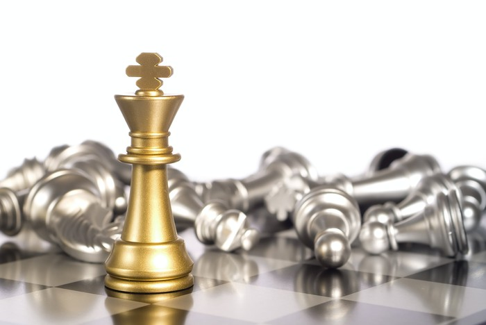 On a chess board, a golden king stands before toppled silver pieces.