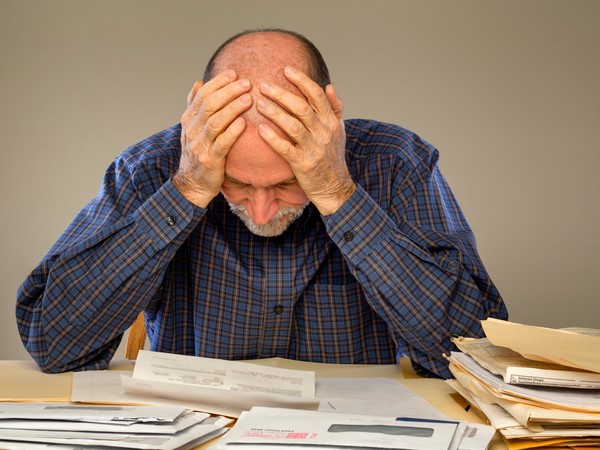 Depressed Senior Man with Stacks of paperwork and envelopes -- GettyImages-168763161