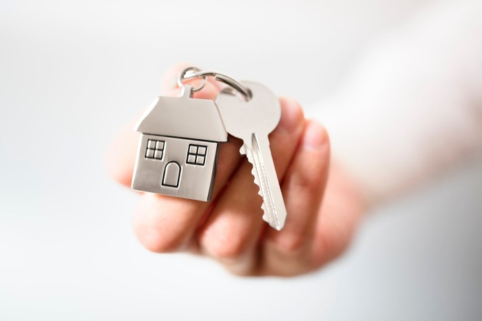 hand holding a key and a miniature house, both on a keyring.