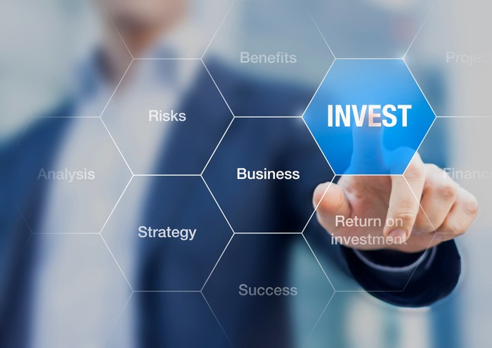 Man pushing hexagonal button, colored blue, with word 'invest' in the center. Other hexagonal buttons have words: risks, analysis, benefits, business, strategy, success, return on investment.