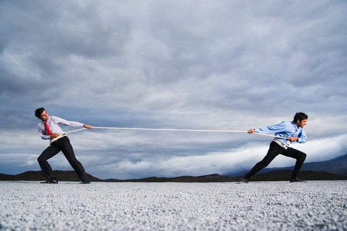 Two men wearing professional attires in a battle of tug-of-war while standing on pebbles under cloudy skies.