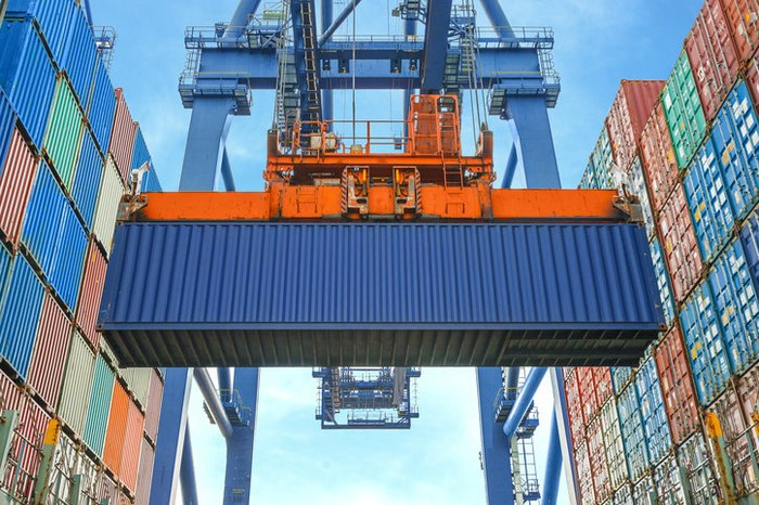 A blue container, surrounded on both sides by stacked containers in varying colors, being lifted at port.