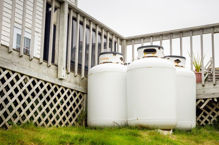 Three white propane tanks on grass and side by side outside of a house next to its deck.