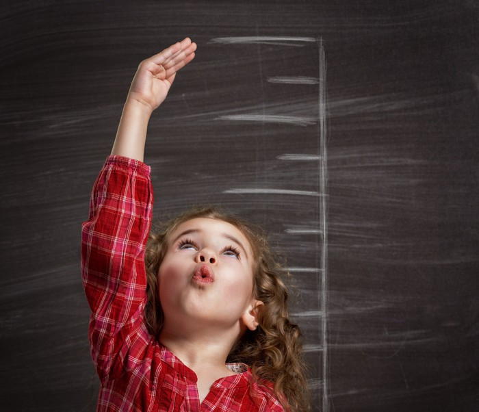 Child raising a hand in front of a chalkboard with measurement lines indicating height