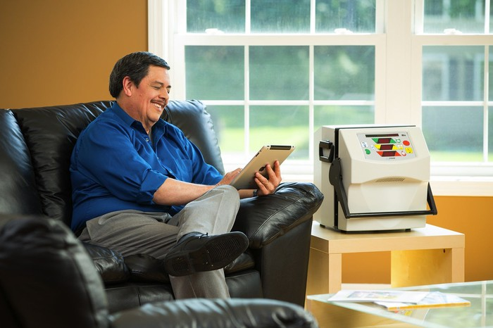 A smiling man sitting in a black leather chair reading, next to a home dialysis machine.