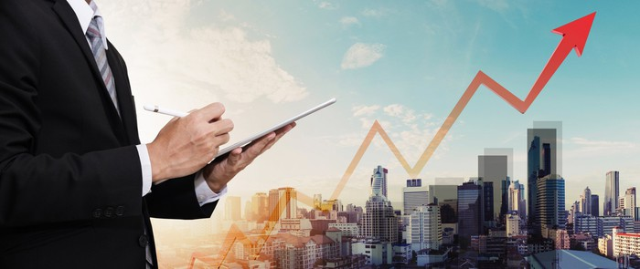 A man in business attire working on a tablet in front of a city skyline with a jagged chart heading upwards.