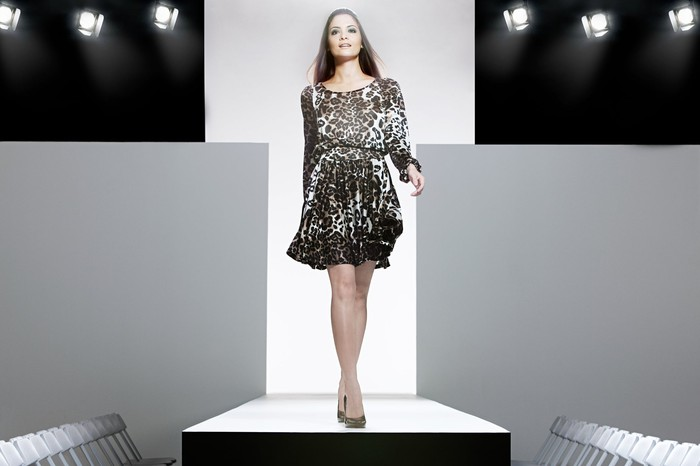 A model in a leopard-print dress walks a runway.