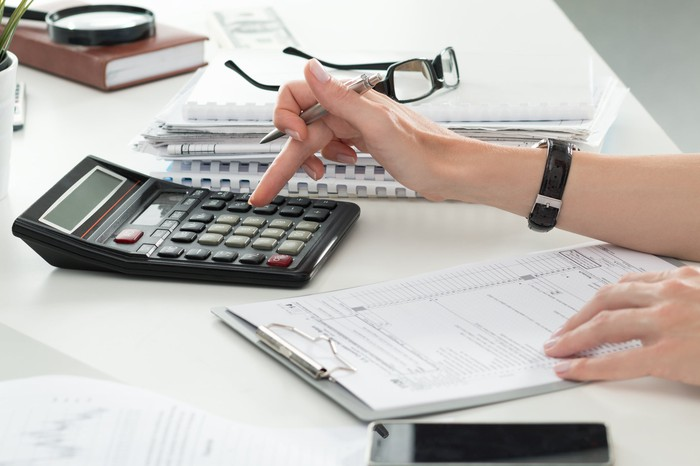 Woman using calculator with forms on a clipboard in front of her