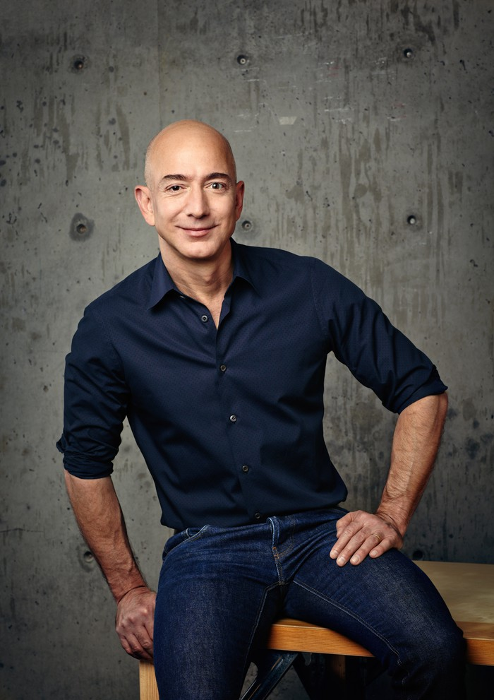 Jeff Bezos sitting on the edge of a table.