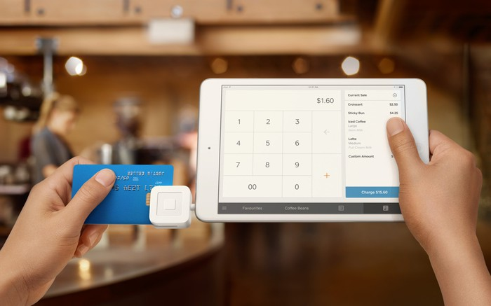 Hands holding a blue credit card and swiping it on a Square register with a chip card reader.
