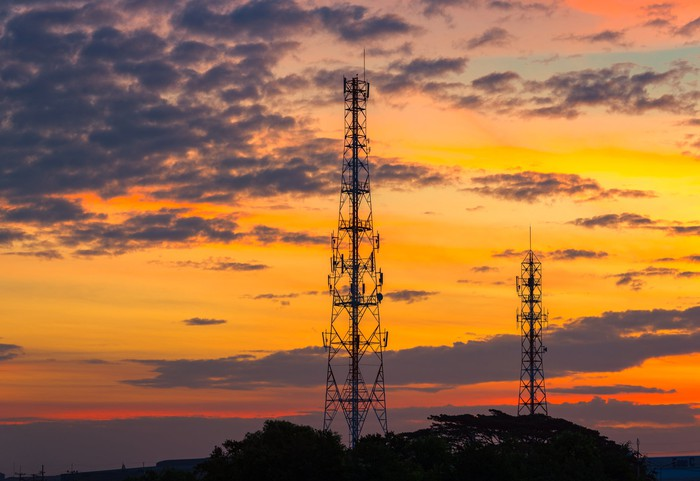 Cell towers with an orange sky and some clouds behind them.