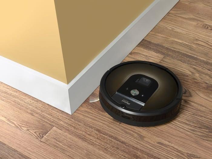An iRobot Roomba vacuum bot on a wood floor.