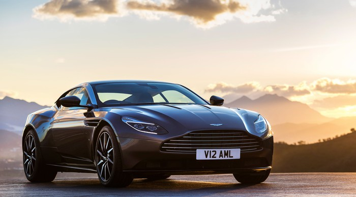 A dark gray Aston Martin DB11, a luxury sports coupe.