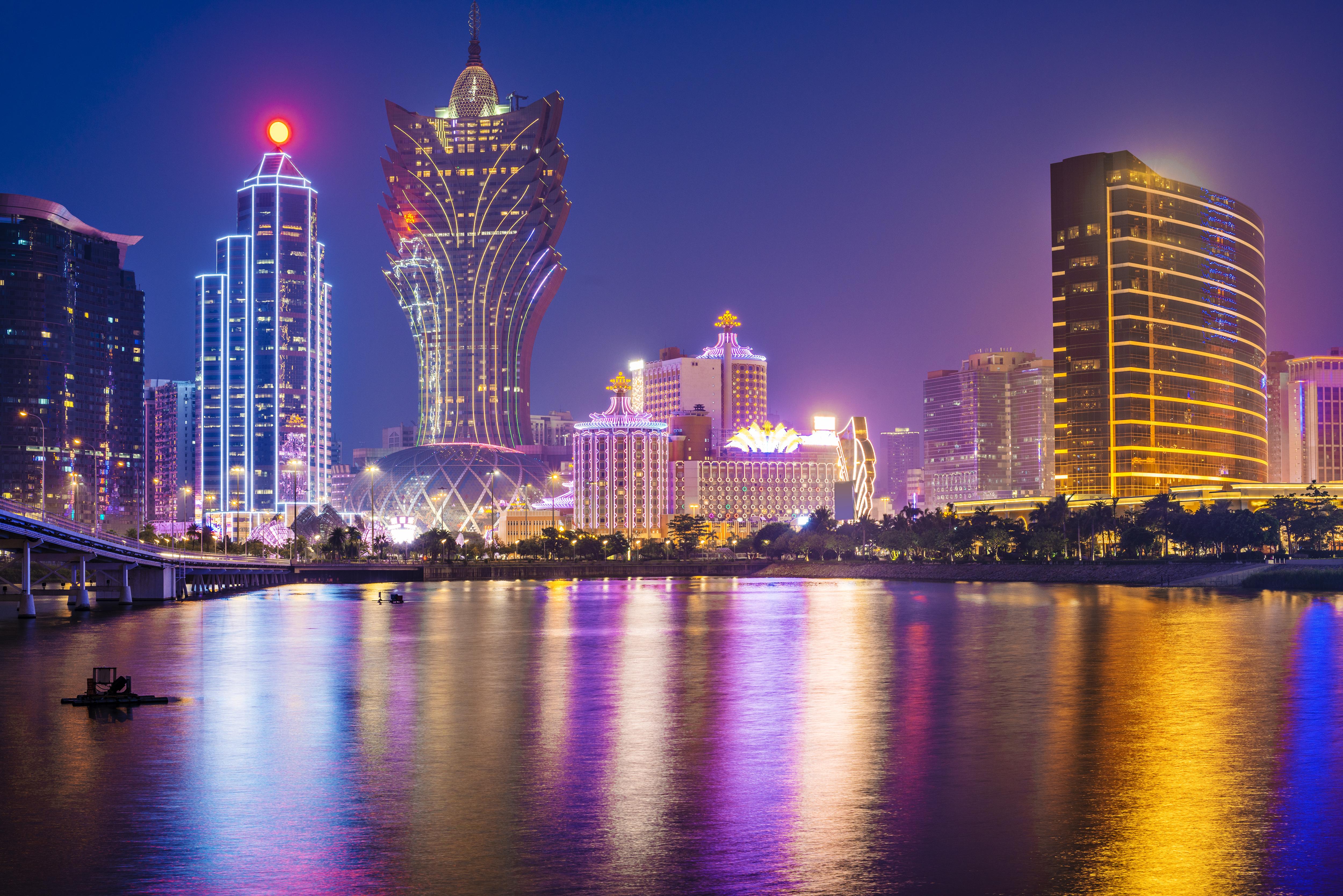 A river reflecting Macau's skyline lit up at night