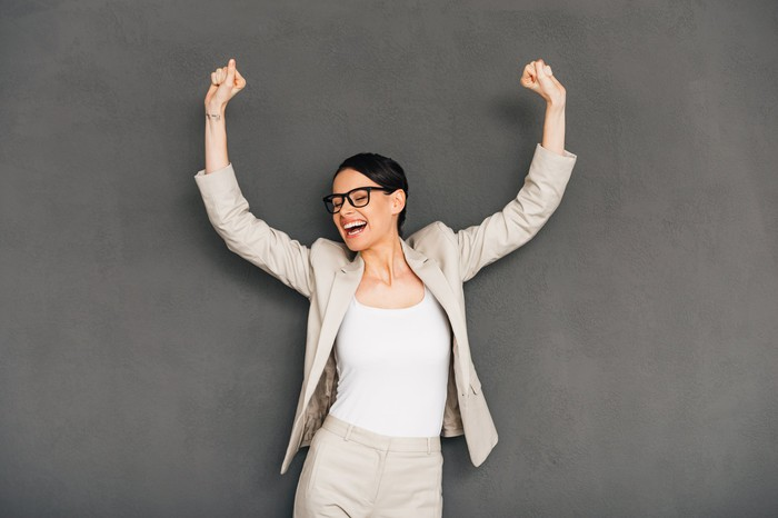 Bespectacled woman in business suit raising her arms in celebration