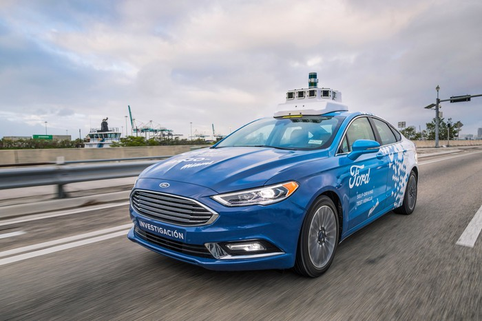 A blue and white Ford Fusion with visible self-driving sensor hardware on a Miami street.