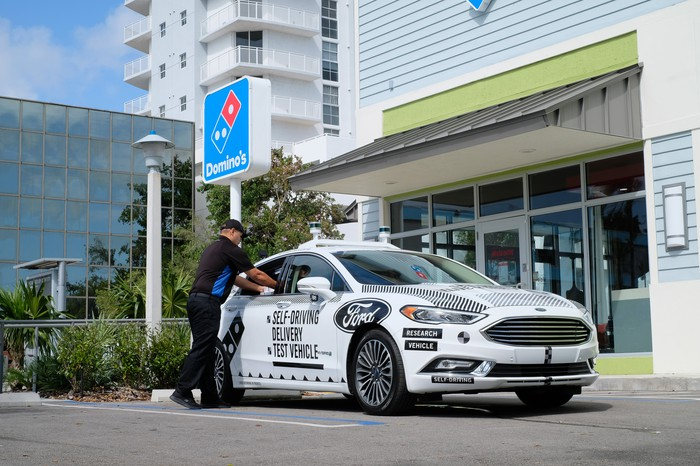 A white Ford Fusion with visible self-driving hardware is parked outside a Domino's Pizza restaurant. A Domino's employee is loading something into the vehicle via its passenger-seat window.
