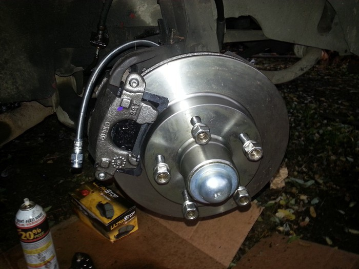Rotor brake assembly with box of brake pads and a bottle of solvent next to the part.