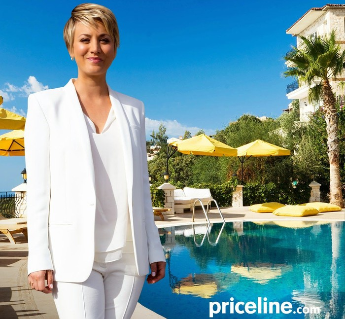 Actress Kaley Cuoco wearing a white suit standing next to a swimming pool in a tropical location.